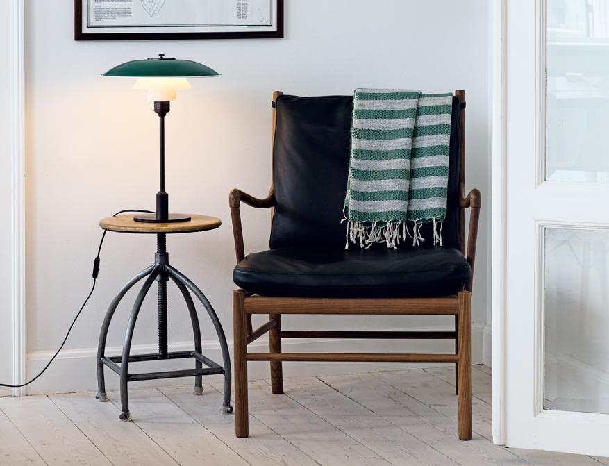 Die PH 3 ½-2 ½ Tischleuchte mit grünem Schirm daneben der Colonial Chair von Ole Wanscher