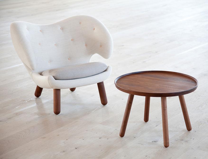 Der Pelican Chair in cremefarbenem Stoff und Beine in Walnuss mit Pelican Table von Finn-Juhl