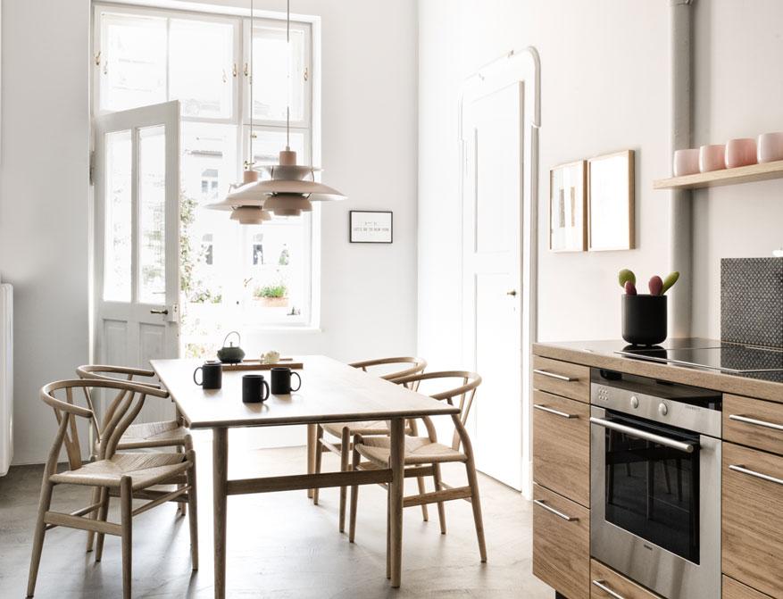 Stühle CH24 Wishbone Chairs am Tisch CH327 beides in Eiche weiß geölt von Hans J. Wegner mit Pendelleuchte PH5 von Poul Henningsen im Falkenberg Apartment Munich