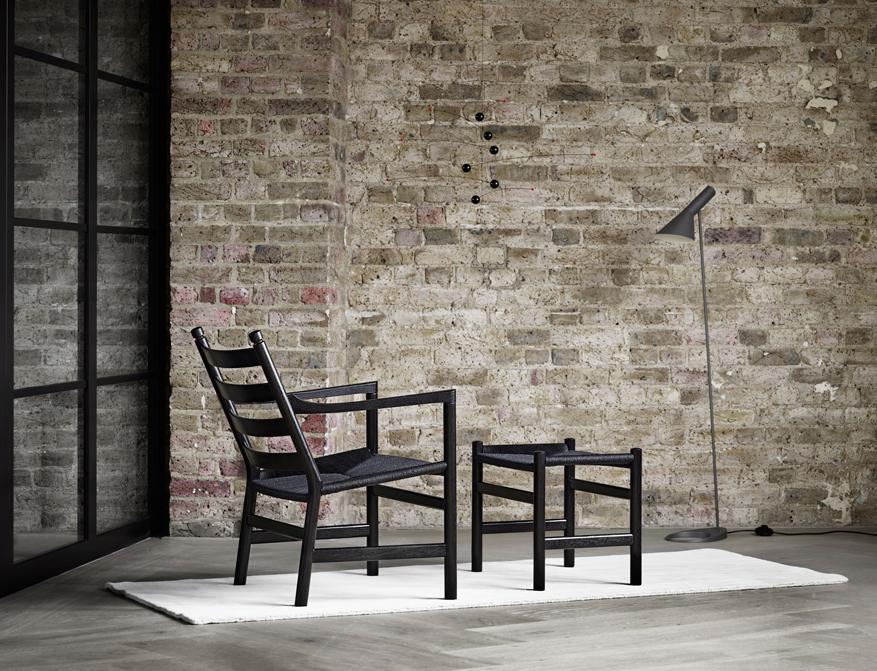 Der Sessel CH44 schwarz lackiert mit schwarzem Geflecht und passendem Footstool CH53 von Hans Wegner