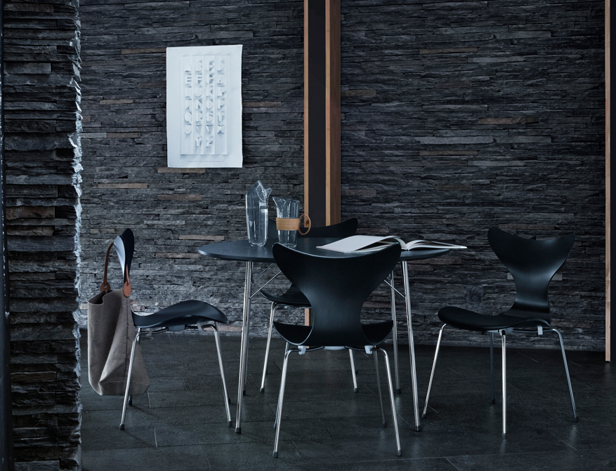 Die Lilie in schwarz mit verchromtem Gestell am Tisch Circular in schwarz alles von Arne Jacobsen