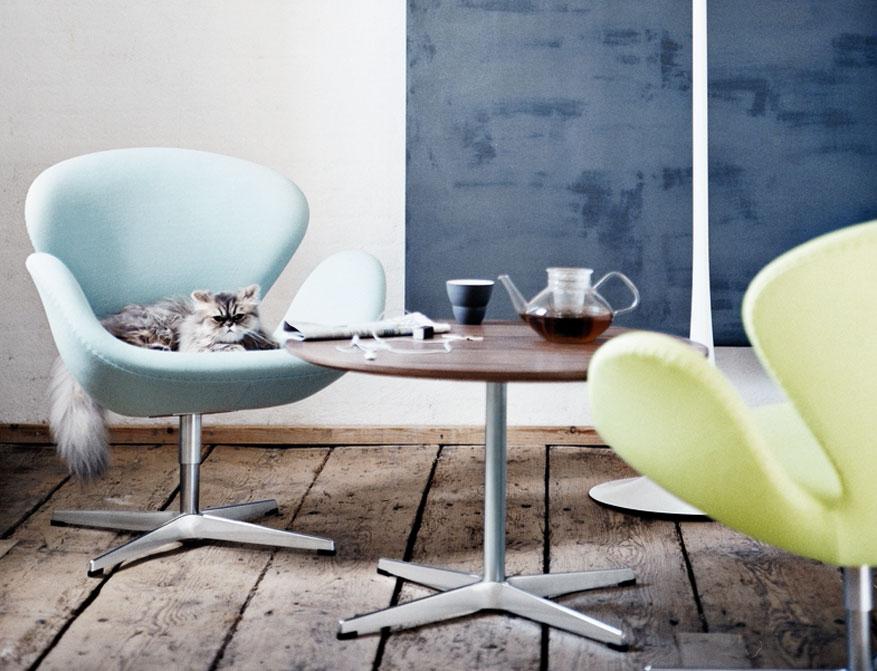 Der Sessel Schwan in hellblauem und hellgrünem Stoffbezug am AJ Coffee Table in Walnuss beides von Arne Jacobsen