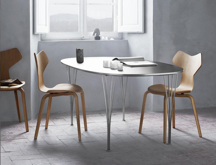 Der Stuhl Grand Prix in Eiche mit Holzgestell am Tisch Super Elliptical beides von Arne Jacobsen