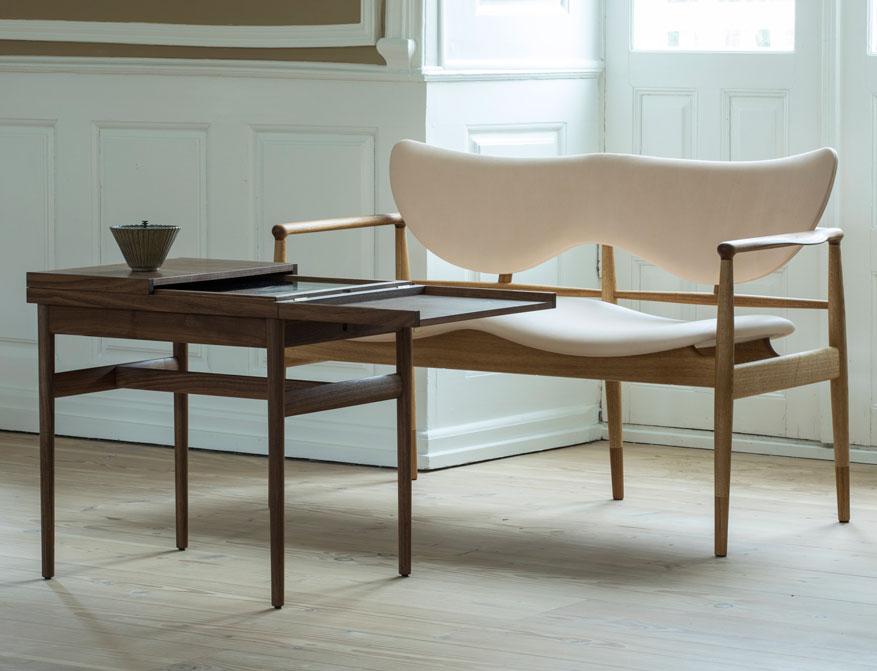 Der Art Collector's Table in Ausführung Walnuss mit Glas einseitig aufgeklappt und das 48 Sofa in Ausführung Eiche/Leder von Finn Juhl