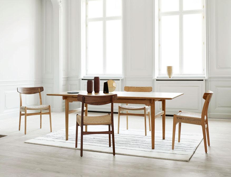 Der Stuhl CH23 von Hans J. Wegner in den Ausführungen Eiche geölt, Walnuss geölt und Walnuss/Eiche geölt am Tisch CH327 in Eiche geölt ebenfalls von Hans J. Wegner