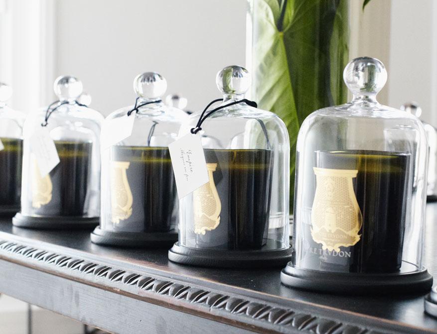 Die Duftkerze von Cire Trudon im Glas mit Cloche aus Glas und einem Untersetzer aus Holz
