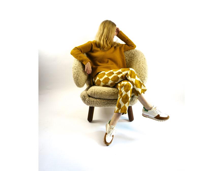 Pullover in Cury mit Hose in Curry/Creme von Odeeh und den Sneakers von Paul Smith aus der A/W 2021/2022 Kollektion mit dem Pelican Chair von Finn Juhl