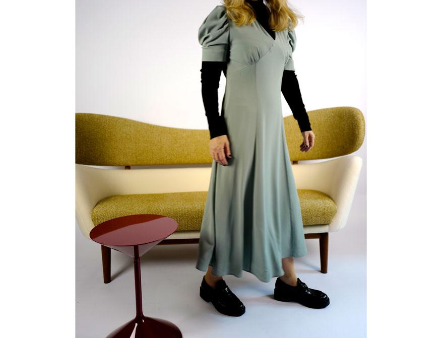 Das Kleid in hellblau aus der Winterkollektion 2021 von Paul SMith mit dem Baker Sofa von Finn Juhl und dem roten Beistelltisch von Zanotta