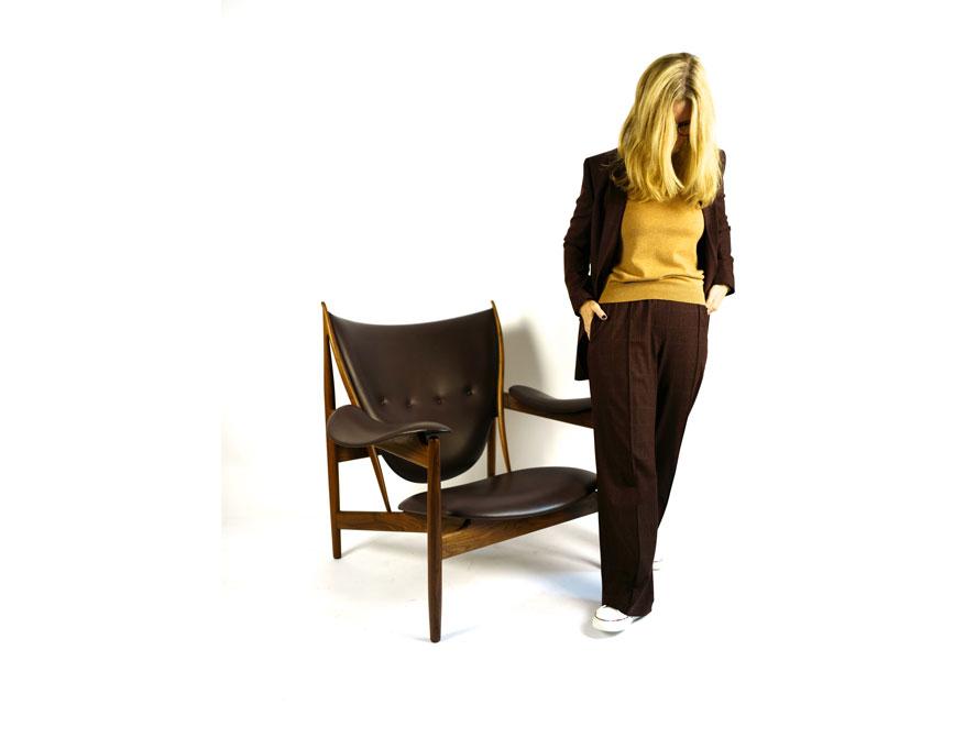 Der Anzug aus Blazer und Hose in beaurdeux-rot kariert mit den weißen Sneaker aus der Winterkollektion 2021 von Paul Smith daneben der Chieftain Chair in Ausführung Leder schwarz und Walnußholz