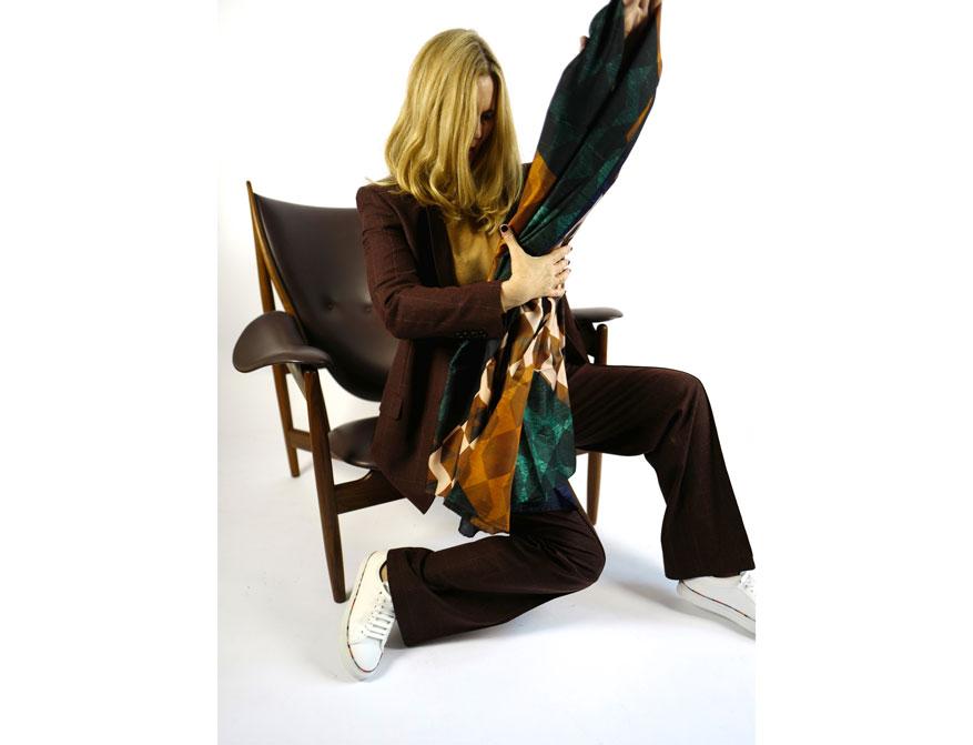Der Anzug aus Blazer und Hose in beaurdeux-rot kariert mit dem Seidentuch aus der Winterkollektion 2021 von Paul Smith und Odeeh daneben der Chieftain Chair in Ausführung Leder schwarz und Walnußholz