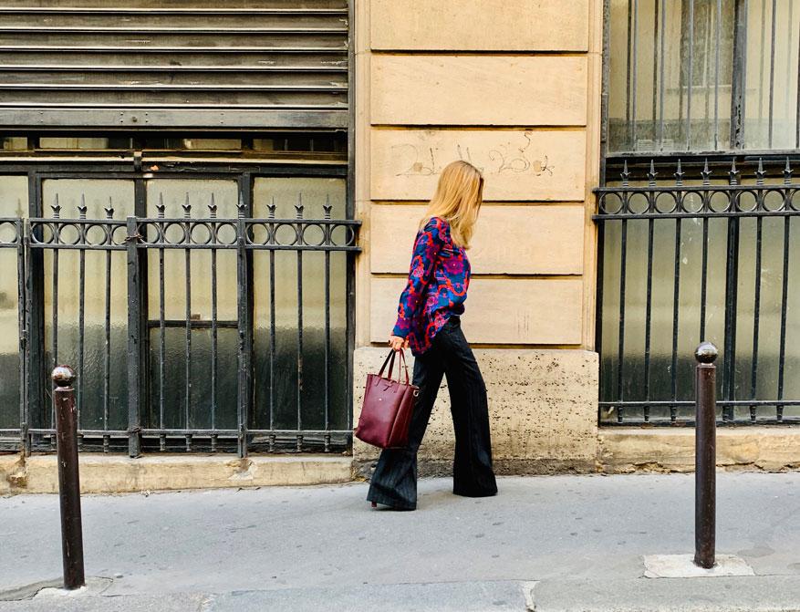 Hose mit Schlag in grauer Schurwolle von Odeeh und blau-rote Bluse aus Seide von Odeeh kombiniert mit einer Ledertasche in Bordeauxrot von Felisi