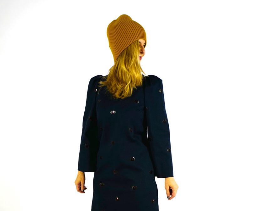 Das Kleid in dunkelblau mit Pailletten-Stickereien und die Mütze in Curry aus Kaschmir aus der Winterkollektion 2021/2022 von Odeeh