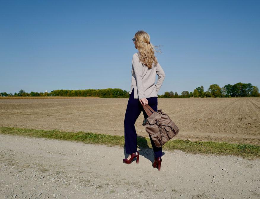 Der Rucksack in braun aus Nylon und Leder von Felisi mit der Hose in dunkelblau und dem Pullover in beige von Johnstons